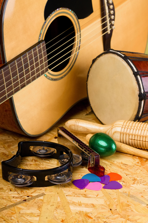 Vertical photo with several musical instruments on wooden OSB board as acoustic guitar with several colorful picks, guiro, harmonica, bongo and others.