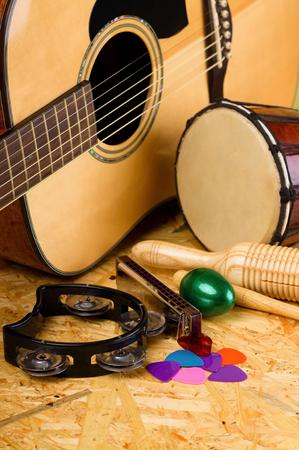Verticale foto met verschillende muziekinstrumenten op houten OSB boord als akoestische gitaar met diverse kleurrijke picks, Guiro, harmonica, bongo en anderen.