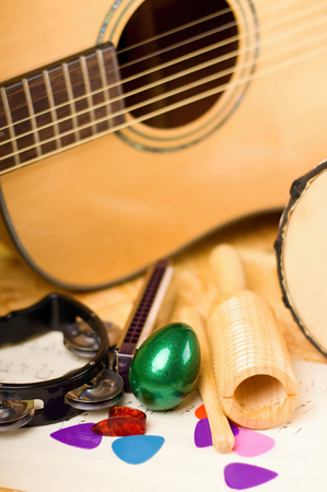 harmonica: Vertical photo of several musical instruments as green egg shaker, guiro, harmonica, bongo and acoustic guitar with few color picks. All is placed on wooden OSB board.