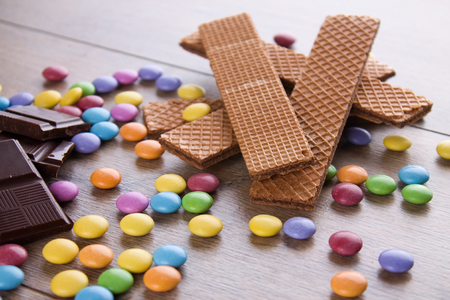 smarties: Horizontal photo of few chocolate biscuits on wooden board with colorful chocolate sweet smarties around. Pieces of chocolate are placed on border. Stock Photo