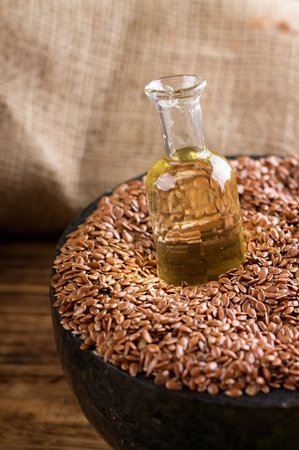gold flax: Vertical photo of marble mortar bowl full of flax seeds on wooden board and with burlap in background. Glass bottle with flax oil is placed in seeds.
