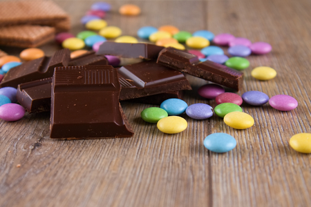 smarties: Horizontal photo with heap of dark chocolate pieces on wooden board with colorful chocolate sweet smarties around and biscuits in background. Stock Photo