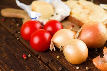 thee: Horizontal photo of thee onions and three tomatoes on wooden board with pepper around in front of piece of romadur ripened cheese and bread with this kind of cheese.