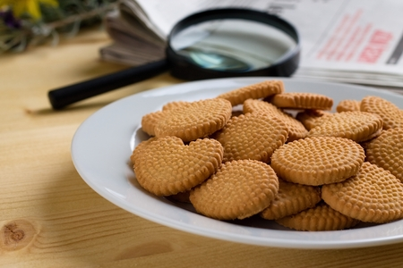 flower shape: Horizontal photo with plate full of crispy lemon biscuits on light wooden plate. Magnifier near to several newspapers are in background. Stock Photo