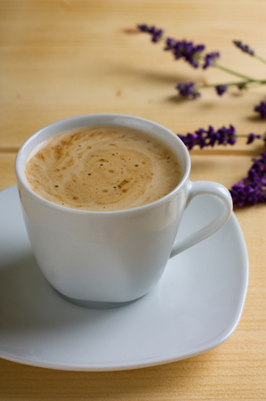 small plate: Vertical photo with cup of coffee with cream on. Cup is placed on small plate and all is on light wooden board. Small sunflowers and lavender flowers are in background.