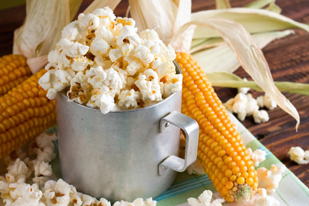 popcorn kernel: Horizontal photo with old worn aluminum cup full of fresh salty popcorn which is too spilled around. Three corncobs are placed on green towel which is on wooden board.