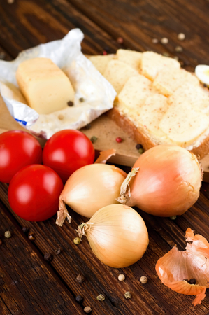buttered: Vertical photo with old wooden table where is placed vegetable next to chopping board with buttered bread with romadur cheese and few quail eggs. Color pepper seeds are around. Stock Photo