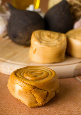 oscypek: Vertical photo with single rolled smoked cheese on ceramic tiles in front of wooden plate with other pieces and various vegetable as black radishes.