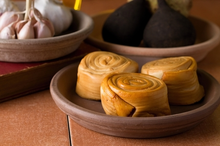 oscypek: Horizontal photo with three pieces of rolled smoked cheese placed in clay bowl. Next two bowls are placed around with vegetable. All is placed on ceramic tiles.