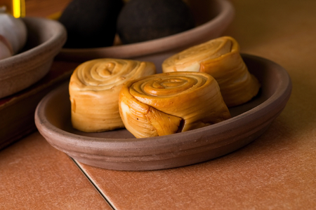 earthen: Horizontal photo with three pieces of rolled smoked parenica cheese which is placed in earthen bowl. Next bowls with vegetable are around on ceramic tiles.