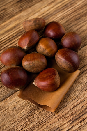 one sheet: Vertical photo with few sweet chestnuts. First one is placed on brown paper sheet. The heap is on old worn wooden board.
