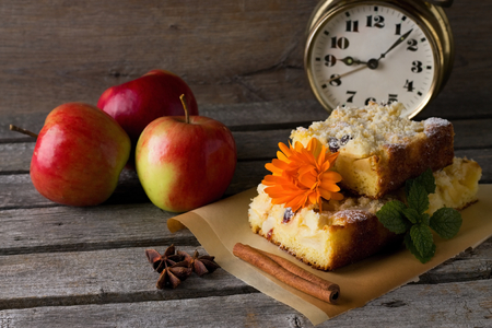 apple orange: Horizontal photo with few slices of apple cake with raisins, marigold bloom and melissa on brown paper with spices. Alarm clock is in background on wooden board. Stock Photo
