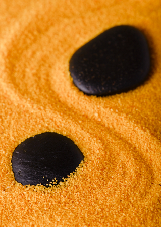 grooves: Vertical photo of two lava stones which are placed in colored yellow sand with curved grooves between them.