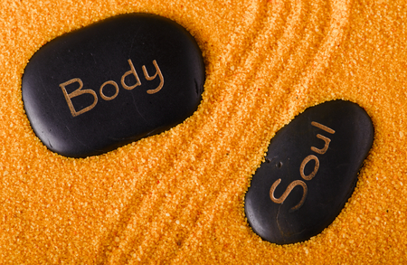energy healing: Horizontal photo with two black lava stones on yellow sand with grooves between them. Stones have lettering Body and Soul written by golden color. Stock Photo