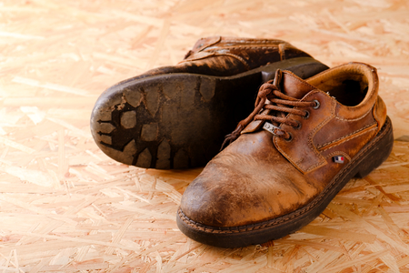 Horizontal photo of two old worn brown leather shoes with damaged laces. Pair of boots is placed on wooden OSB board. One boot is spilled.
