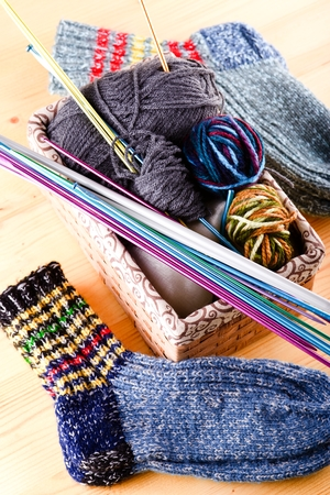 Vertical photo of box full of wool clues and several knitting needles and other accessories. Two pair of socks are around on wooden board. Stock Photo