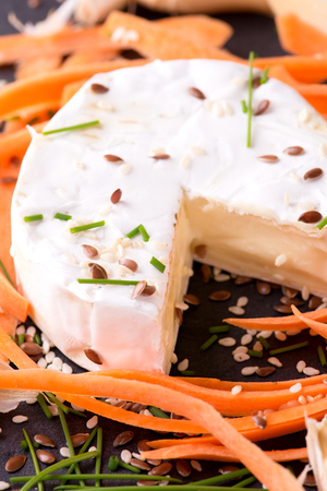 flux: Vertical photo of camembert cheese with several carrot shavings around. Sesame and flux seeds are spilled around together with green chive and garlic. Food is placed on slate plate.