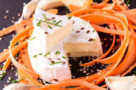 flux: Horizontal photo of camembert cheese with several carrot shavings around. Sesame and flux seeds are spilled around together with green chive and garlic. Food is placed on slate plate.