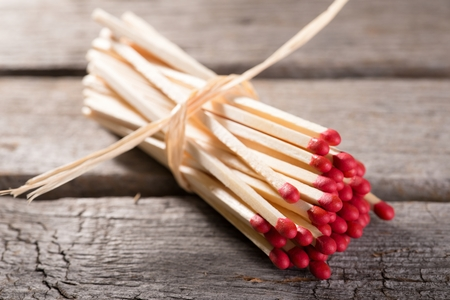 red heads: Horizontal photo with Bunch of long wooden matchsticks with red heads which are bonded by piece of yellow dry straw. Bunch is placed on old worn wooden board with grey color.