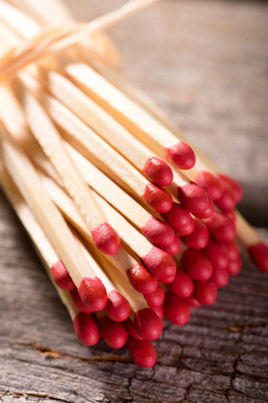 red heads: Vertical photo with Bunch of long wooden matchsticks with red heads which are bonded by piece of yellow dry straw. Bunch is placed on old worn wooden board with grey color.