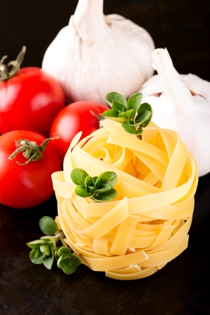 thee: Vertical photo of single portion of fettuccine paste with several sprigs of green oregano herb, two white garlics and thee red tomatoes. All is placed on old black metal plate with worn surface. Stock Photo