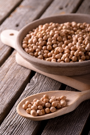 legume: Vertical photo. Legume on wooden spoon. Dry chickpeas. Clay plate full of chickpeas. Plate on chopping board. Spoon on wooden board. Wooden board full with grey worn surface.