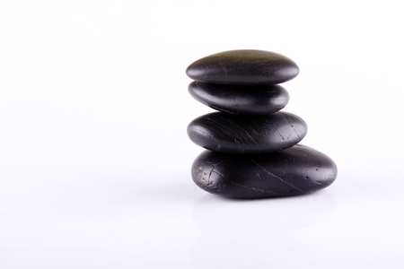 black stones: Horizontal photo of black lava stones. Black stones stacked at each other. Few stones on white board. Relaxing lava stones placed isolated on white background. Stock Photo