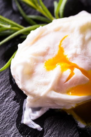 Vertical photo of single pouched egg with few water bubbles on surface after boiling and flowing orange yolk. Egg is placed on black slate stone with nice surface with red ketchup and green herb.