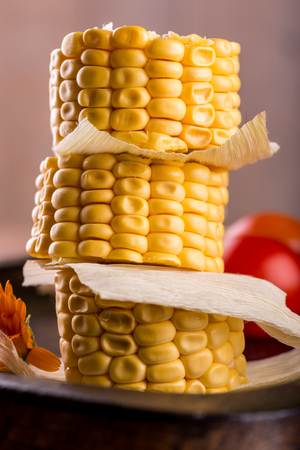 Vertical photo of three pieces of yellow sweet corn. Food is placed on a stack with leaves between. Corn is on dark wooden plate and wooden board with tomatoes and bread. Stock Photo