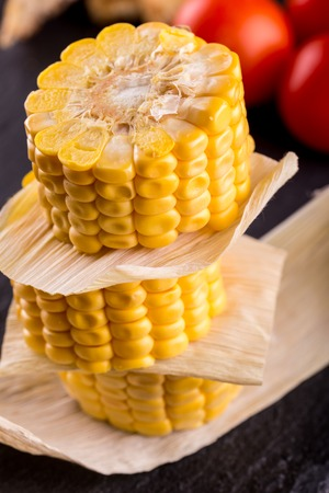 Vertical photo of three pieces of yellow sweet corn. Food is placed on a stack with leaves between. Corn is on black stale stone and wooden board with tomatoes and bread. Stock Photo