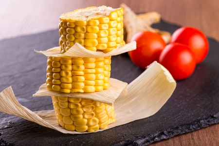 Horizontal photo of three pieces of yellow sweet corn. Food is placed on a stack with leaves between. Corn is on black stale stone and wooden board with tomatoes and bread.