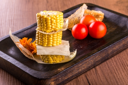 Horizontal photo of three pieces of yellow sweet corn. Food is placed on a stack with leaves between. Corn is on dark wooden plate and wooden board with tomatoes and bread.