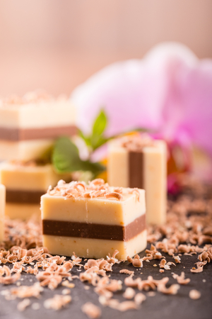 Vertical photo of several pieces of sweet nougat which is made from three layers with different brown colors.