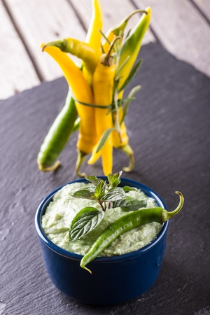 bonded: Vertical photo of wasabi dip in small blue bowl. Green chili pepper is placed on dip with green mint herb. Bunch of yellow peppers with herb rosemary bonded by chive on slate stone. Stock Photo