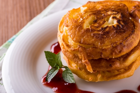 Horizontal photo of few cinnamon apples coated in pancake dough. Sweet food placed on white plate with spilled red fruit jam. Piece of green mint herb next to tower. Plate on cloth and wooden board.