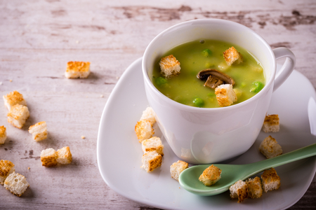 Horizontal photo of split pea soup. Green soup in white coffee cup with saucer and green ceramic spoon. Several bread croutons spilled on plate and around on white wooden board. Stock Photo
