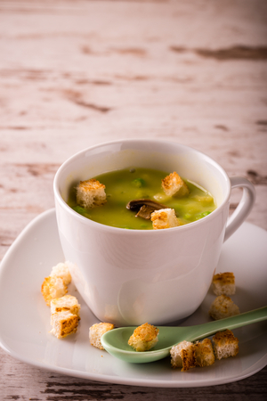 Vertical photo of split pea soup. Green soup in white coffee cup with saucer and green ceramic spoon. Several bread croutons spilled on plate and around on white wooden board.