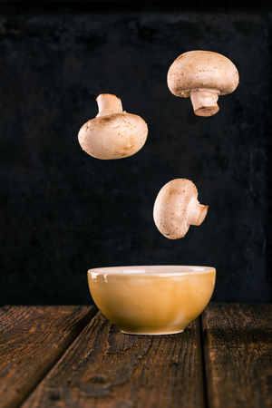 Vertical photo of three floating champignons which fell into the yellow bowl. Mushrooms are frozen in the air over the ground. Bowl is on dark wooden brown board. Background is black tray.
