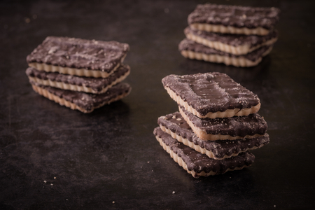 textrured: Horizontal photo with few stacks of square biscuits with chocolate on one side. Each stack consists of four or free pieces. Sweets are placed on dark black baking tray with textrured worn surface. Stock Photo