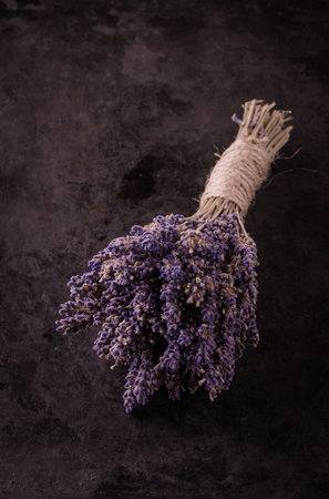 bonded: Vertical photo with single bunch of lavender flower bonded by natural cord with vintage mood. Purple blooms are dry as a rest of plant. Black dark worn baking tray is used as background. Stock Photo