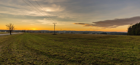Horizontal wide screen photo of landscape immediately after sunset. Autumn fall scene of field or meadow with grass and several electrical pillars and wires. Sky is cloudy and with warm colors.
