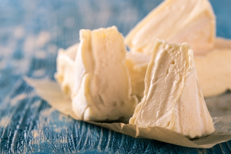 penicillium: Horizontal photo of several portions of camembert. Cheese is cut to smaller triangles which are placed together on crumpled paper sheet and on worn wooden board with blue paint.