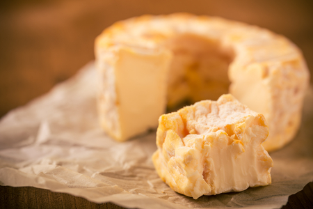 Horizontal photo of whole special camembert cheese with golden color and hole in the middle with cut off single portion which is bitten. Cheese is placed on crumpled paper and dark wooden board.