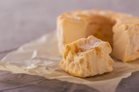 Horizontal photo of whole special camembert cheese with golden color and hole in the middle with cut off single portion which is bitten. Cheese is placed on crumpled paper and grey textured board.