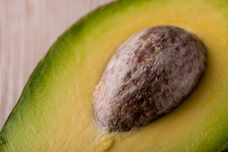 Horizontal photo with detail of big brown avocado core still placed in half of green yellow fruit. Light wooden board is used as a background. Stock Photo