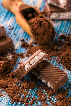 Vertical photo with several broken pieces of brown chocolate with light creamy filling. Cocoa in vintage wooden spoon is next to sweets and spilled around on blue wooden board. Stock Photo