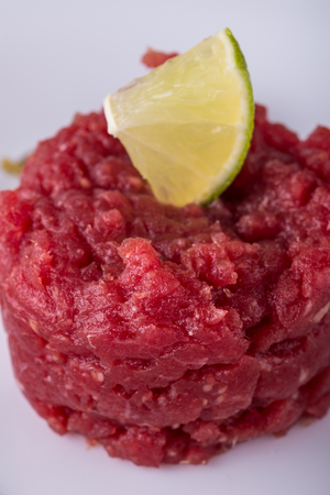 Vertical photo with single portion of red beef tartar steak. Meat is placed on white plate. Piece of green lime is on the top of portion.  Stock Photo