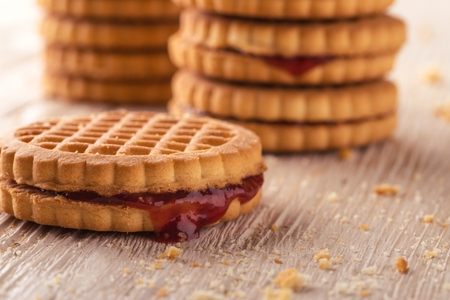 greased: Horizontal photo of several stacks of golden biscuits. Biscuits are with red berry homemade marmalade. Biscuits are placed on light white wooden board. Several crumbs are spilled around.