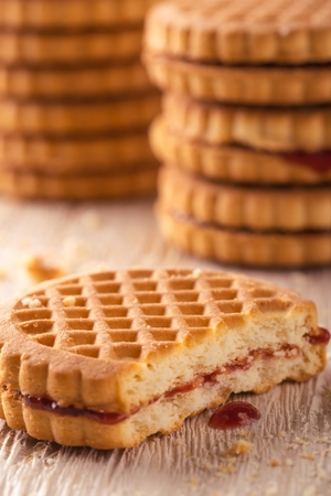 greased: Vertical photo of several stacks of golden biscuits. Biscuits are with red berry homemade marmalade and one is tasted. Biscuits are placed on light white wooden board. Several crumbs are spilled around. Stock Photo