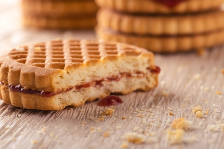 greased: Horizontal photo of several stacks of golden biscuits. Biscuits are with red berry homemade marmalade and one is tasted. Biscuits are placed on light white wooden board. Several crumbs are spilled around.